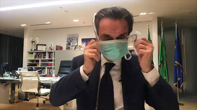 Italy's Lombardy Governor Attilio Fontana puts on a protective mask as he announces on Facebook that...