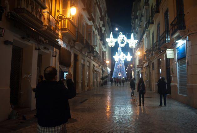 Un hombre toma una fotografía de las luces de Navidad, en Málaga durante la