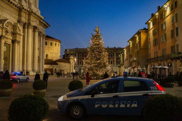 Two police car overlook the crowded Duomo Square in Brescia, Italy on November 29, 2020. As the covid...