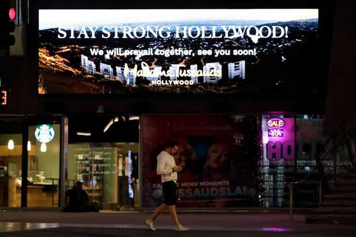 "A man walks under a sign that reads ""Stay Strong Hollywood"" along Hollywood Boulevard on Thursday, April 2, 2020, in Los Ange"