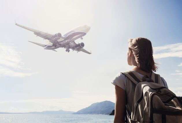 Young girl looking at the flying plane above the sea, travel
