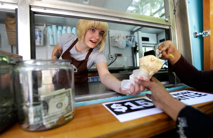 Caitlyn Faircloth, a worker with Molly Moon's Homemade Ice Cream, hands out free ice cream in 2014. Business across the