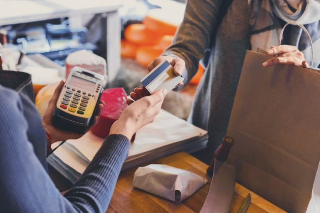 Retail, credit card payment service. Customer paying for order of cheese in grocery