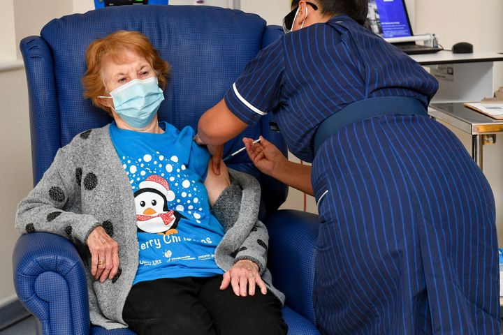 Margaret Keenan, 90, the first patient in the UK to receive the Pfizer-BioNTech COVID-19 vaccine, administered by nurse May Parsons at University Hospital, Coventry, England, Tuesday Dec. 8, 2020.