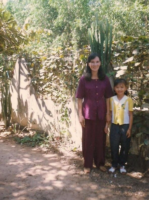The writer, then about eight years old, stands with her mother outside their home in Vietnam.