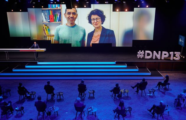 Özlem Tureci (l) and Ugur Sahin (r) shown on screen during an awards ceremony in early