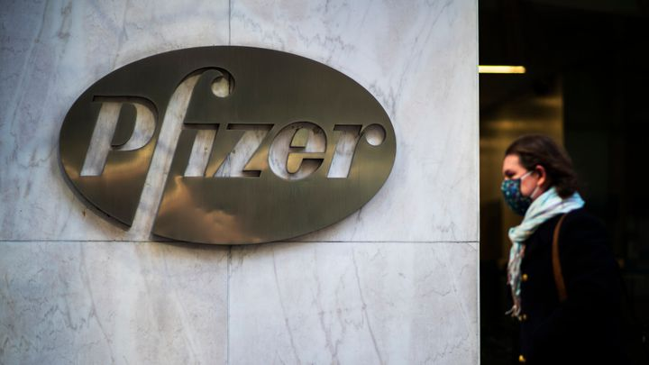 A woman walks in front of Pfizer headquarters in New York City.
