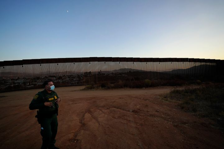 A U.S. Border Patrol agent looks out along newly replaced border wall sections near Tecate, California, back in September.