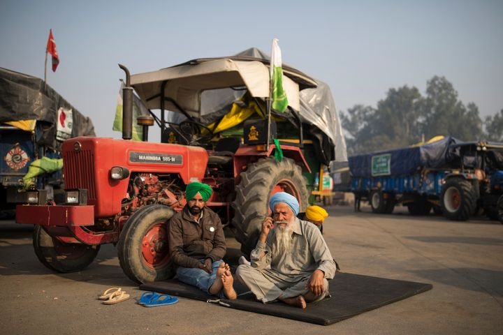 Protesting farmers Raghuvir Singh, right, and Gurnam Singh bask in the morning sun while sitting next to their tractor parked on a highway, during a protest at the Delhi-Haryana state border, India, on Dec. 1, 2020.