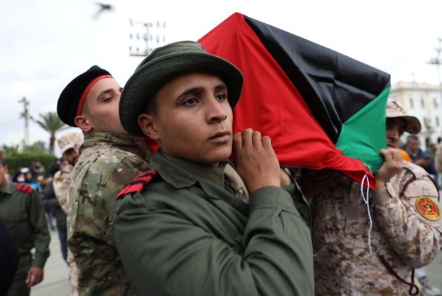 Libyan security personnel carry a coffin on Jan. 5, 2020, during the funeral of people...
