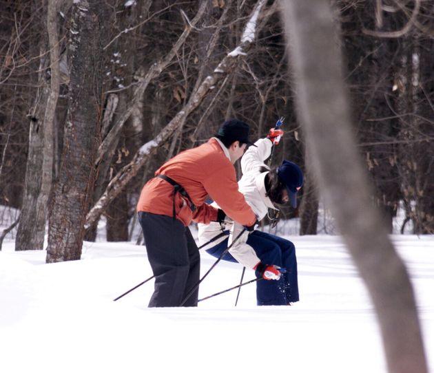 クロスカントリースキーで散策中に転んでしりもちをつき、天皇陛下に抱き起こされる皇后さま(北海道千歳市の青葉公園)=1999年02月20日