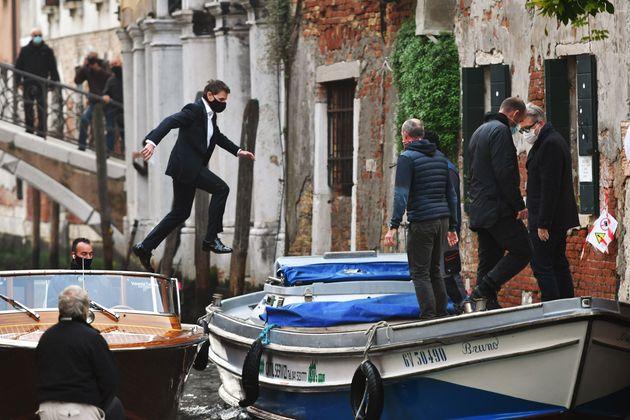タクシーボートとからタクシーボートへと飛び移るトム・クルーズさん=2020年10月20日、イタリア・ベニス