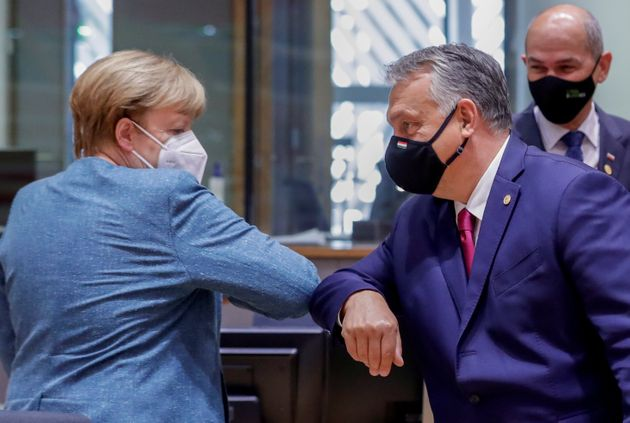German Chancellor Angela Merkel bumps elbows with Hungary's Prime Minister Viktor Orban at the start...