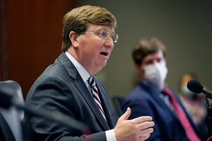 Gov. Reeves is seen explaining his rationale for not ordering a statewide mask mandate last month while seated next toS