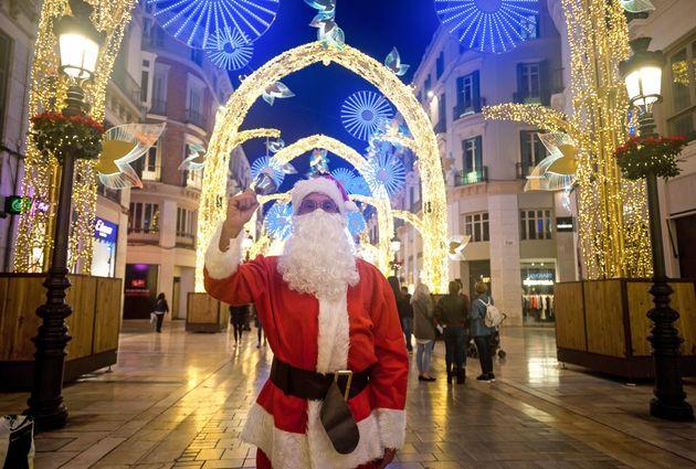 Un hombre disfrazado de Papa Noel camina por el centro de