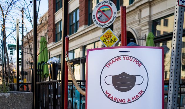 A sign encouraging customers to wear a mask at the entrance of a business in downtown Boise, Idaho, in