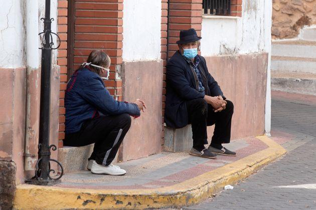 Dos personas hablan con mascarillas y respetando la distancia de seguridad en una calle de La Puerta...