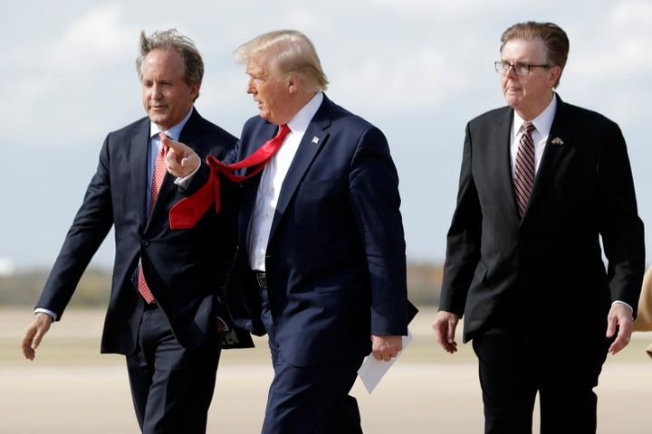 President Donald Trump walks with Texas Attorney General Ken Paxton (left) and Texas Lt. Gov. Dan Patrick (right) at Au