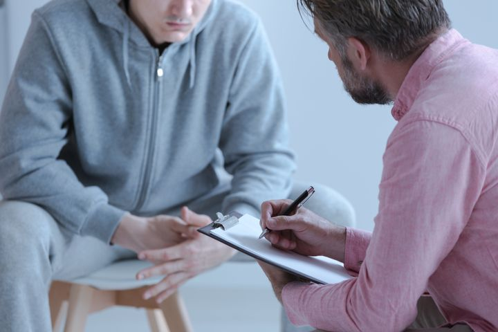 Un orientador educativo atiende a un adolescente.