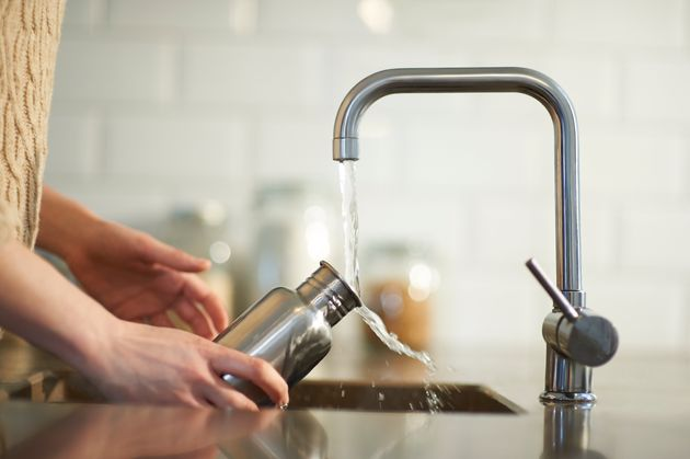 A woman cleans a plastic free and reusable water bottle in a kitchen sink, close
