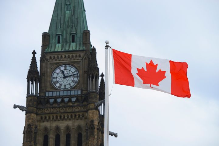 A Canadian flag flies by Parliament Hill in Ottawa on March 13, 2020.