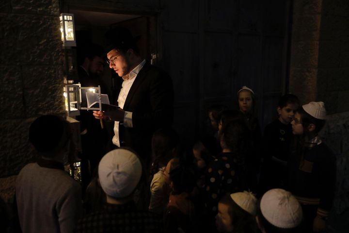 A Jewish man lights candles in observance of Hanukkah in Jerusalem, Thursday, Dec. 10, 2020.