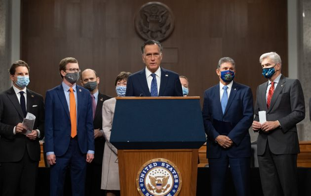 Sen. Mitt Romney (R-Utah), center, speaks alongside a group of Democrat and Republican members of Congress...