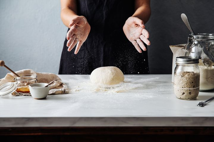 Midsection of woman throwing dough on flour over marble counter. Female is preparing sourdough bread. She is in kitchen.