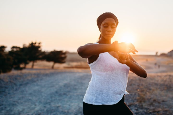 A fit and active African American woman on an evening jog in Washington state, enjoying the beauty of the outdoors and vitality she feels from a healthy lifestyle.