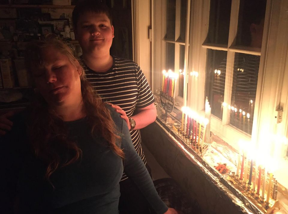Rabbi Zvi Solomon's wife and son with Hanukkah candles on a previous