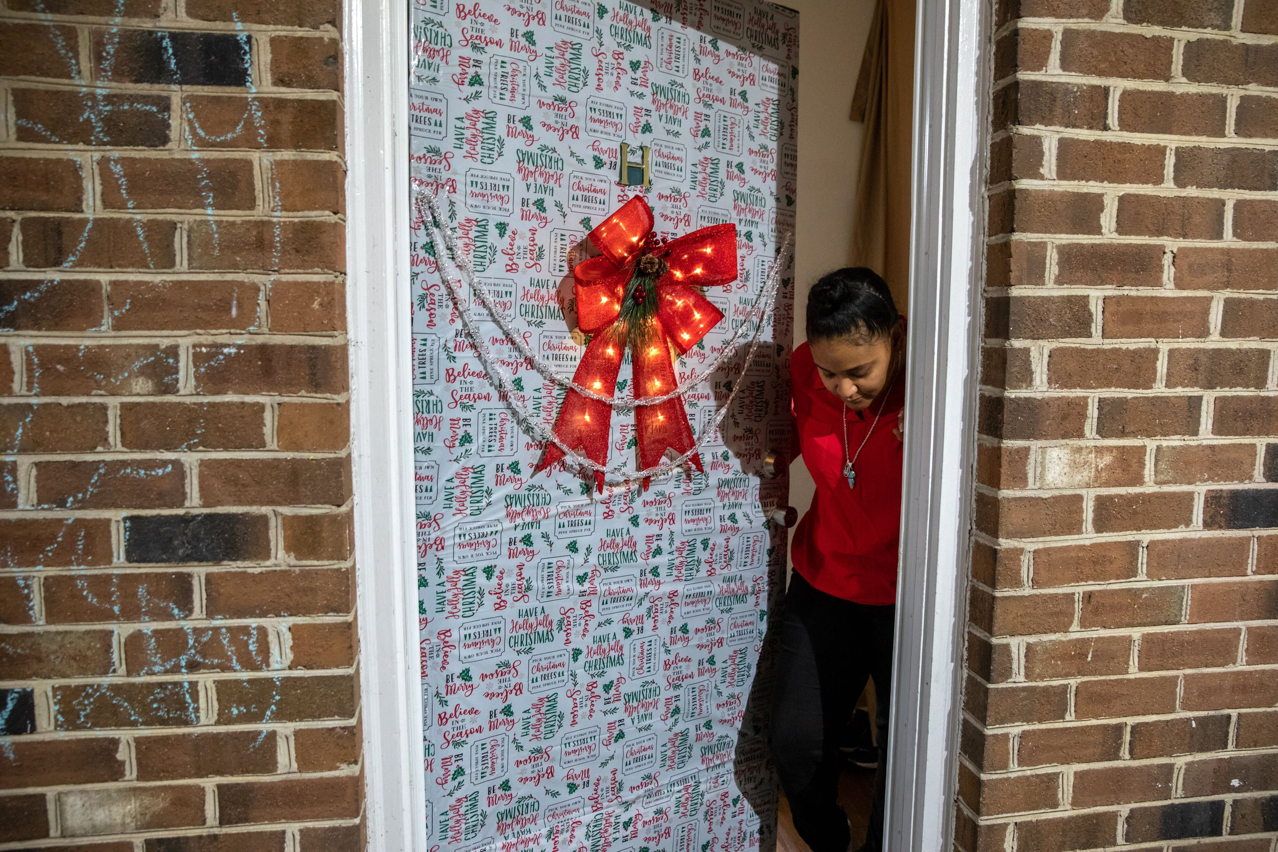 Nawaal Walker stands at her decorated door in her home in Durham, North Carolina. Walker, a single mother of seven, is facing