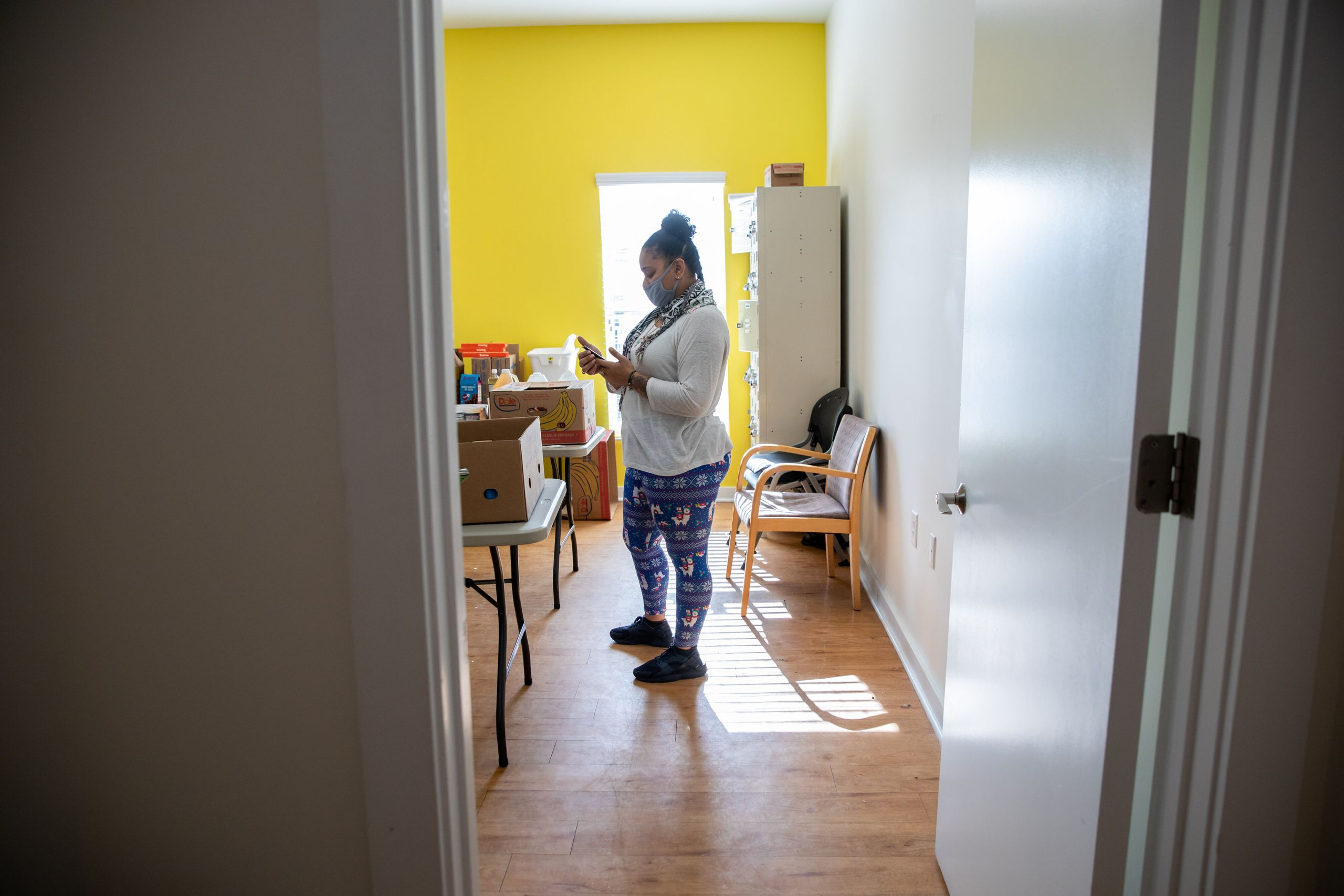 Nawaal Walker checks her phone while working her job at a mental health treatment center.
