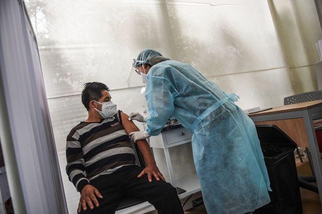 Una sanitaria prepara a un voluntario para recibir la vacuna china de Sinopharm contra el COVID-19 en...