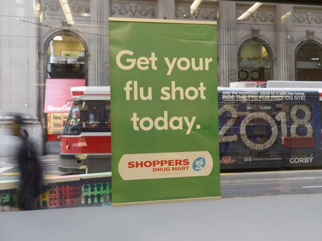 A man walks past a sign for flu shots in Toronto on Jan. 9,