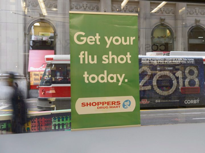 A man walks past a sign for flu shots in Toronto on Jan. 9, 2018.