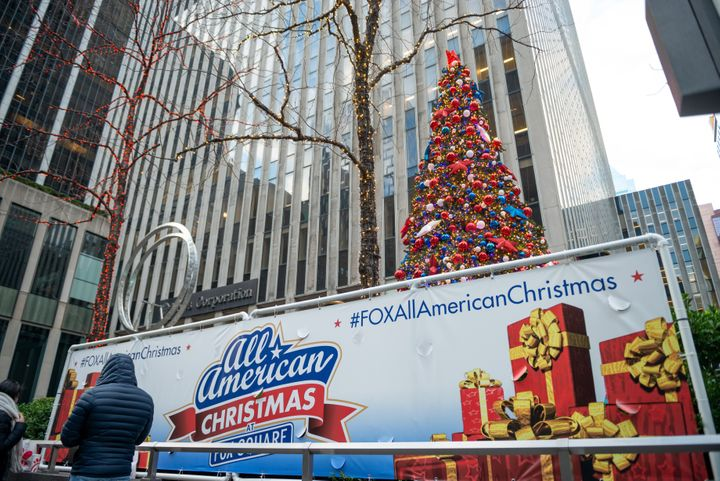 "An ""All American Christmas at Fox Square"" sign near Christmas decorations in front of the News Corporation building in New Yo"