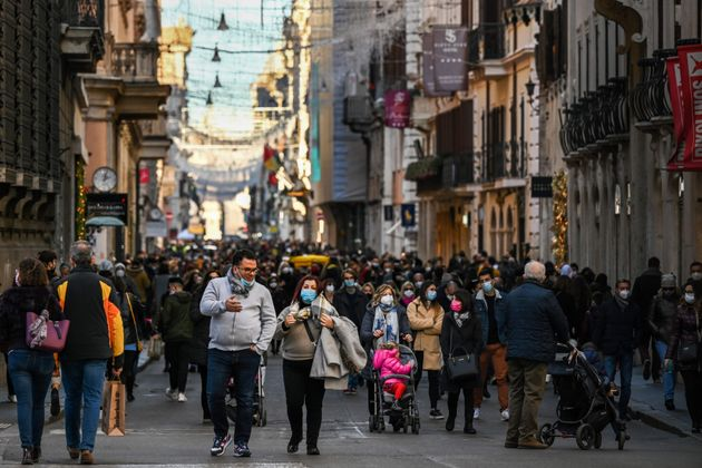 People wearing a face mask gather on the Via del Corso main street for their Christmas shopping on December...