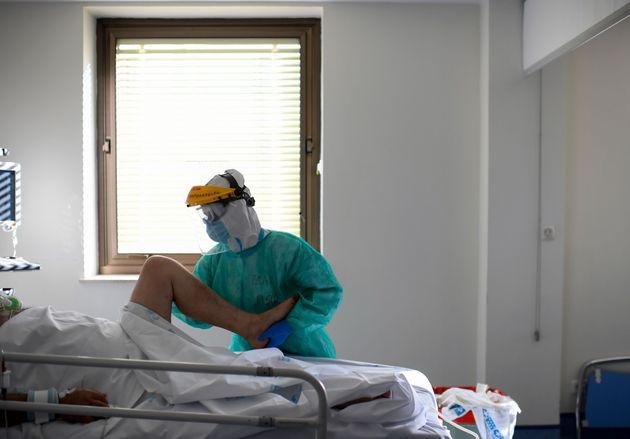 Un sanitario atiende a un paciente en el hospital Ramón y Cajal, Madrid, durante la