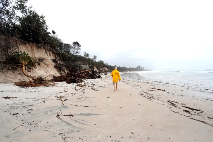 A man walks along the stretch of coastal areas seen disappeared due to erosion along the beach side, December 14, 2020 in Byron Bay, Australia.
