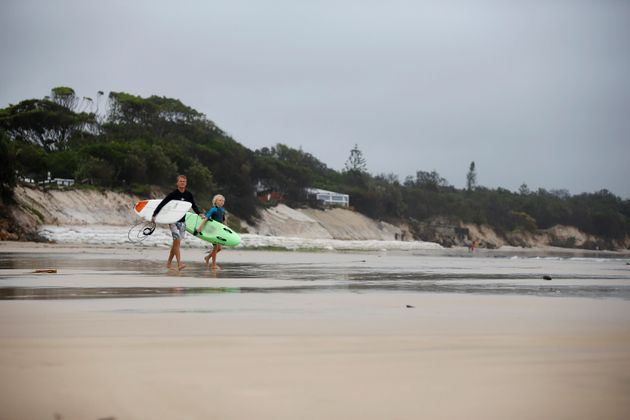 Surfers walk past the stretch of coastal areas seen disappeared due to erosion along the beach side,...