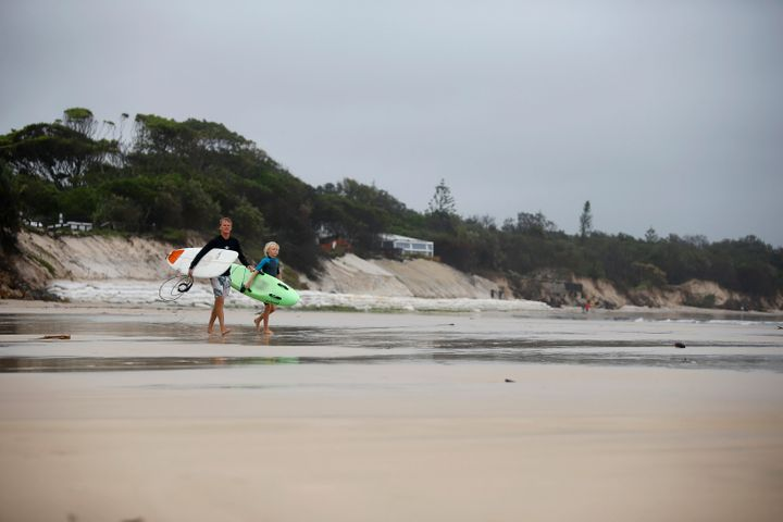 Surfers walk past the stretch of coastal areas seen disappeared due to erosion along the beach side, December 14, 2020 in Byron Bay, Australia.