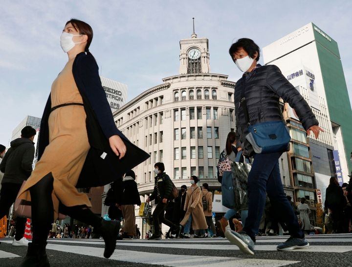 People cross an intersection in Tokyo's Ginza district on December 13, 2020. Japan's daily coronavirus cases have exceeded 3,000 for the first time while the government delays stricter measures for fear of hurting the economy ahead of the holiday season.