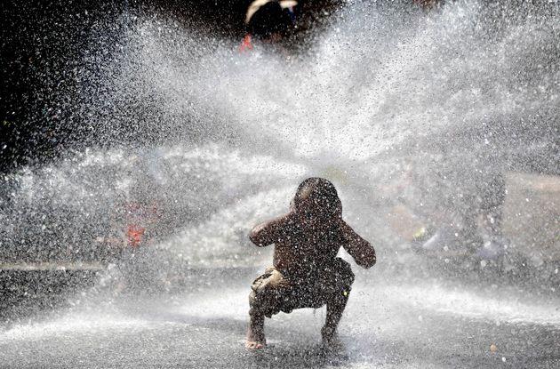Un niño busca refugio del calor extremo frente a un cañón de
