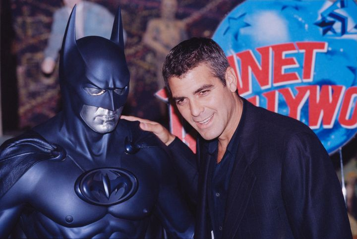 """George Clooney poses with a model of Batman during a photocall for """"Batman and Robin"""" at Planet Hollywood in 1997."""