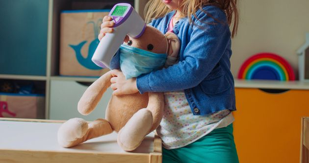 Toddler girl using electronic non-contact thermometer for bunny soft toy in the kids room. Pandemic COVID-19