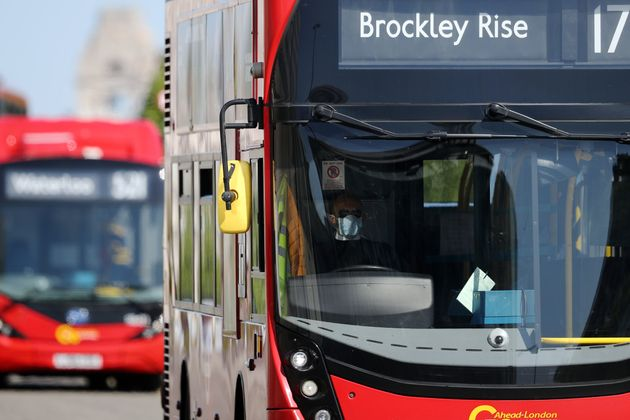 A bus driver wearing a face mask drives over Waterloo