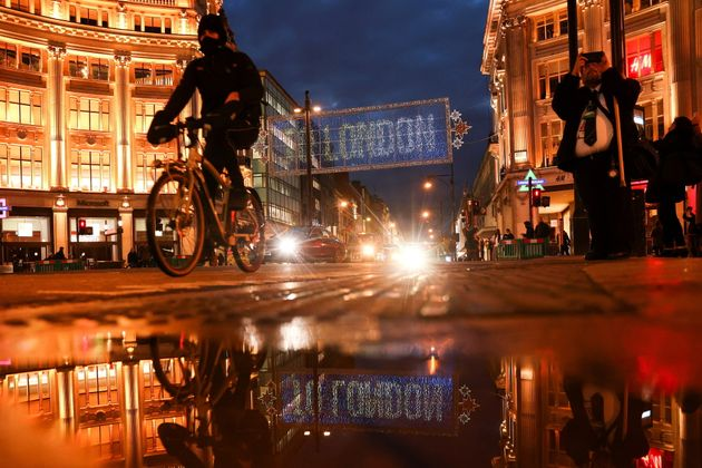 A cyclist moves cycles past the Christmas lights on Oxford Street amid the coronavirus disease (COVID-19)...