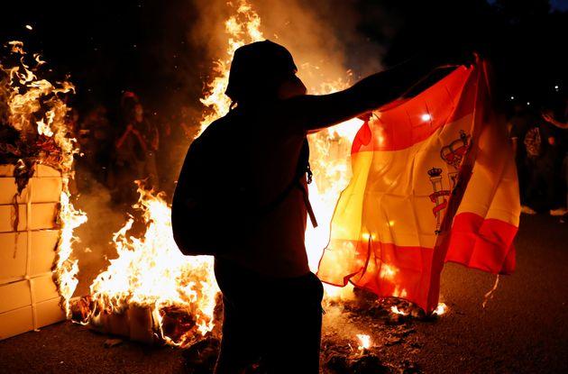 Un independentista catalán, prende una bandera española durante unas protestas en