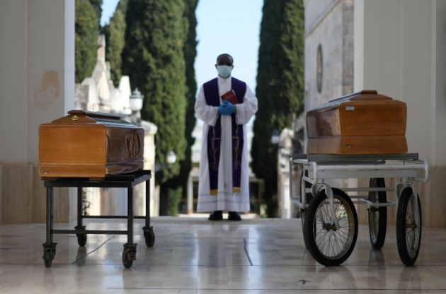 Coffins of two victims of coronavirus disease (COVID-19) are seen during a burial ceremony in the southern...