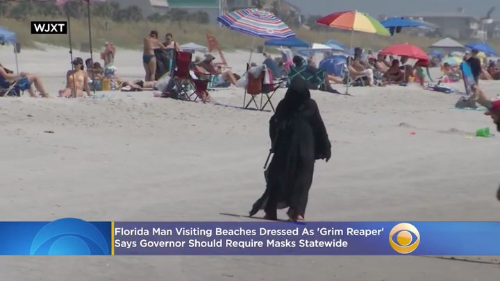 Daniel Uhlfelder walks along a beach in a Grim Reaper outfit in hopes of encouraging people to stay home to prevent COVID-19